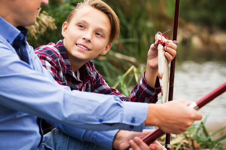 Glad teenager boy showing his father catch fish he holding in hands