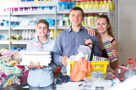 Happy couple and teenager with household goods purchase in the store