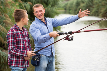 Glad father and teenager son fishing together from water side on river