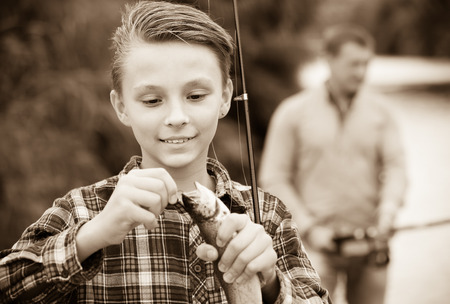 portrait of cheerful smiling teenager boy holding catch fish on hook outdoors