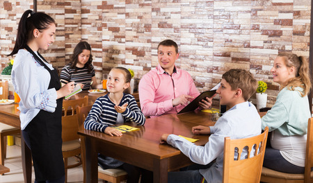 Glad young waitress taking order from guests and writing into note Foto de archivo
