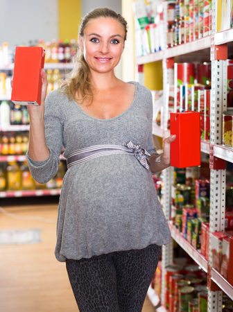 Pregnant woman 30-35 years old is demonstrating her choice in grocery department.