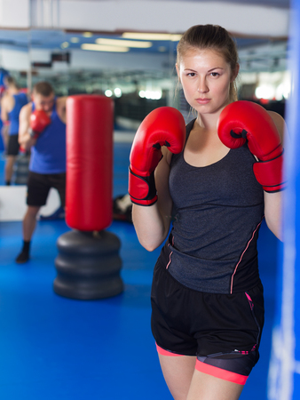 Portrait of young female boxer training in gym Stock Photo