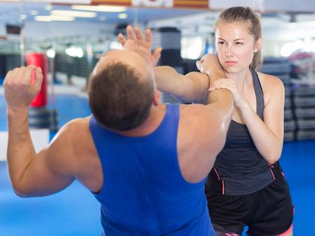 La donna adulta sta combattendo con l'istruttore sul corso di autodifesa per la donna nel club sportivo Archivio Fotografico - 90459232