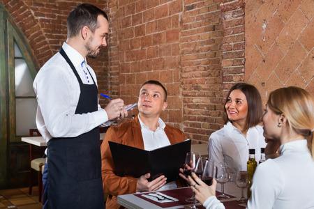 Mężczyzna kelner przyjmuje zamówienia od gości w wiejskiej restauracji