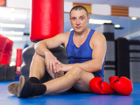 Adult male boxer is sitting on the floor after training in gym Stock Photo