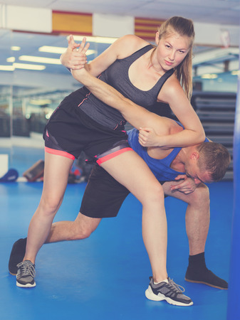 Cheerful female is fighting with trainer on the self-defense course for woman in sport club