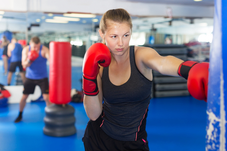 Portrait of young woman boxer training in fitness center