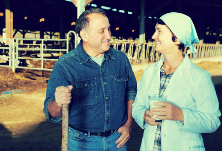 smiling couple quality experts are standing in uniform and checking the quality of milk at the farm