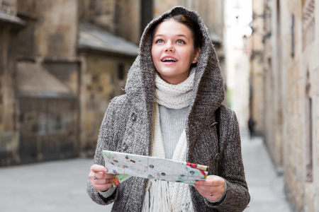 young female in the historical city center in hood with map Stock Photo