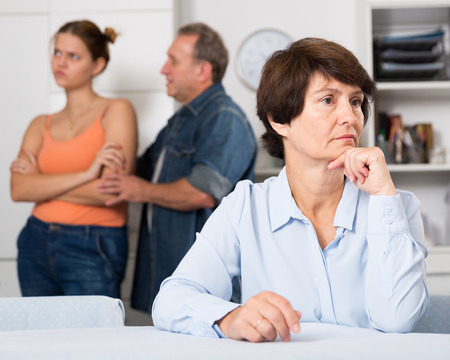 Upset mother is sitting at the table and her family is sympathying with her at home.