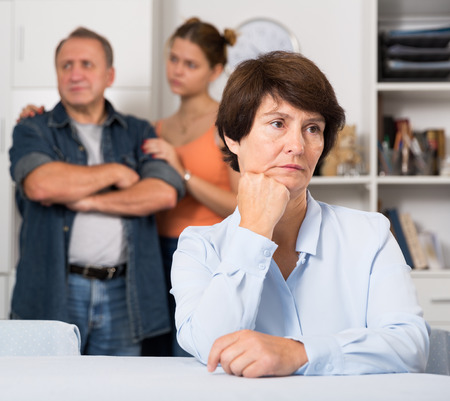 Man and his daughter are sympathying their sad mother who is sitting at the table at home.