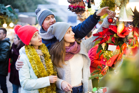 russian family of three with teenage girl choosing  floral decorations  at market. Shallow depth of focus