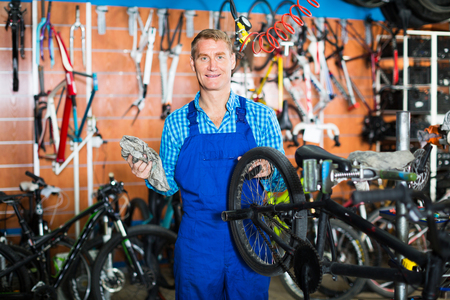 Adult cheerful man in uniform working with bicycles wheels andti res in sport shop
