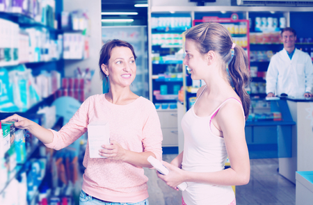 Portrait of smiling woman with daughter teenager shopping healthcare products in drug store