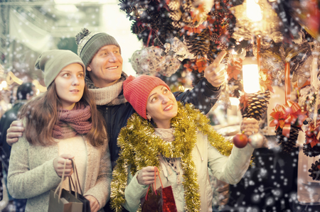 married couple with a teenage daughter at Christmas market outdoors