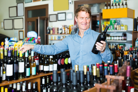 interested middle-aged man customer buying bottle of wine in wine house