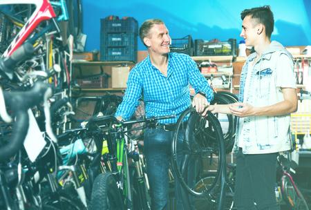 smiling customer choosing new wheel lid for bicycle in sport hypermarket