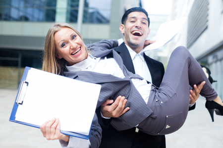 Boss is carry woman manager on hands because they are satisfied of successful contract outdoors near office. Archivio Fotografico