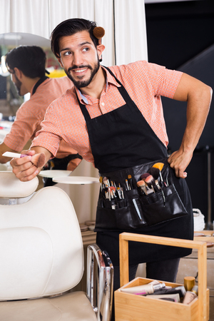 Cheerful sexy man visagiste standing with brushes near chair Stock Photo