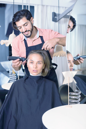 Portrait of happy positive smiling man hairdresser cutting womans hair in salon