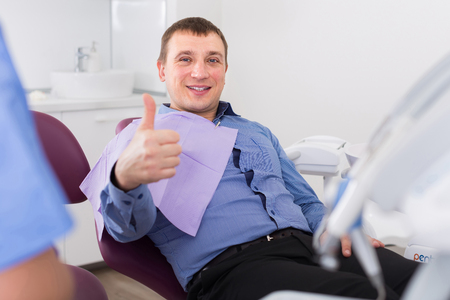 positive patient male thumbs up about work of dantist in medical room
