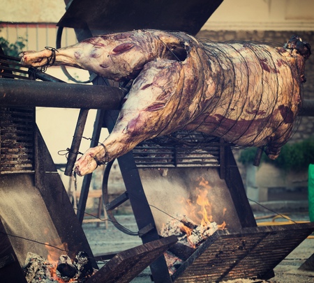 Close-up carcass of whole bull roasting on spit at Medieval Fiesta in Besalu, Spain