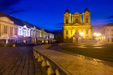 Illuminated Unirii Square with Roman Catholic Dome at dusk, Romania