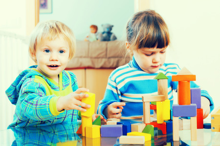 happy children playing with wooden toys in home