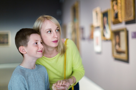 Smiling happy cheerful  mother and son regarding paintings in halls of museum