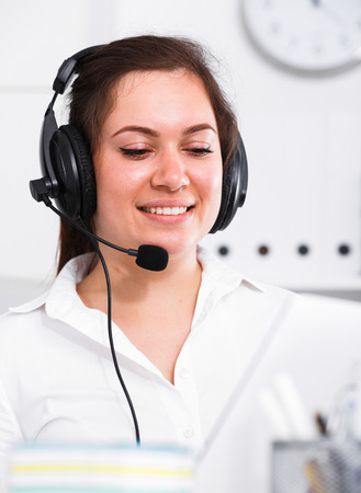 Young female worker productively operating at call-center