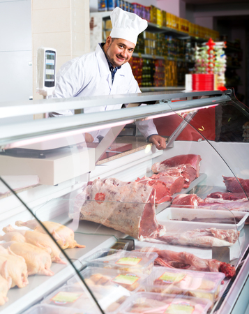 Portrait of cheerful male butcher in kosher section at supermarket