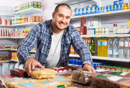 positive male customer choosing nuts and grain in average food shop Stock Photo