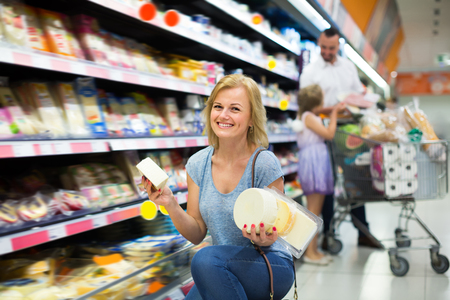 Happy female customer selecting cheese in refrigerated section in hypermarket