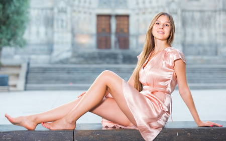 young cheerful austrian girl in romantic dress sitting in town Stock Photo