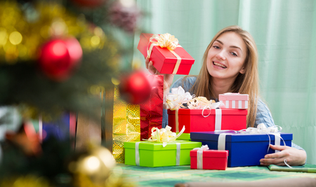 Happy young woman preparing presents for Christmas for guests