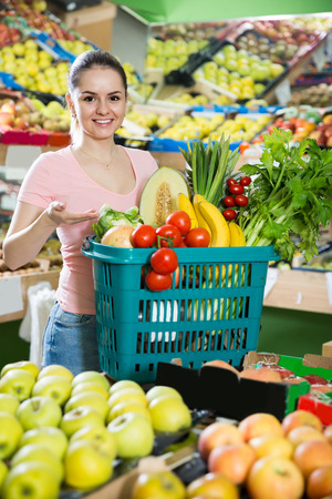Young bulgarian  woman with basket with fresh greengrocery enjoying purchases in vegetable store