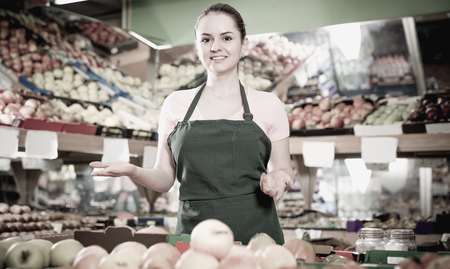 Friendly attractive germany salesgirl proposing fresh fruits and vegetables in supermarket