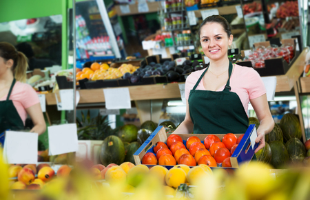 Smiling female grocery worker in apron offering fresh persimmons Stock Photo