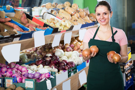 Portrait of young friendly saleswoman in store with onions in hands