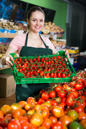 Friendly attractive saleswoman with crate with tomatoes in supermarket