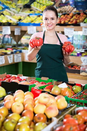 Positive happy cheerful  female grocery worker in apron selling fresh red tomatoes Stok Fotoğraf