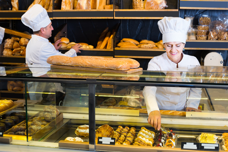 Portrait of professional mature bakers with fresh bread smiling in bakery Banco de Imagens