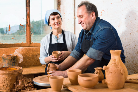Two cheerful  potters in the process of work at the workshop Stock Photo