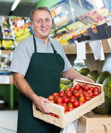 adult seller is offering red tomatos in the market.