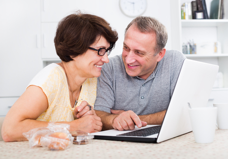 Laughing mature man and woman discussing while looking at laptop together in a home. Focus on both persons