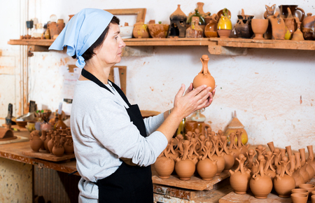 Happy elderly female master among the finished products in the pottery workshop Stock Photo