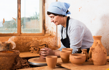 Glad mature female  potter working at workshop