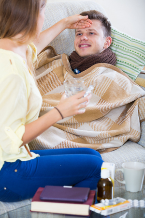 Portrait of sick guy with flue and nursing girl indoors
