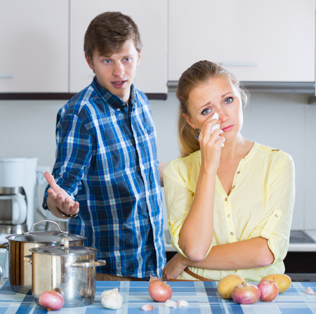 Upset man and frustrated housewife having bad argument indoors